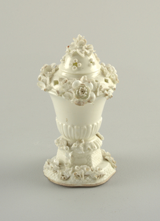 "In the form of a vase with vertical gadrooning. Modelled flowers on the pierced dome lid and octagonal base. Unpainted ""blanc de chine"" surface. Ceramic body without glaze visible at base."