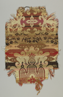 Carpet fragment showing a partial design of vaguely Islamic medallions with framing leaves and stems. In shades of beige, tan, brown, red, pink and black.