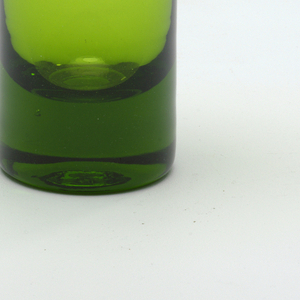 In olive -almost chartreuse- green, with cylindrical base before an angled bottle-form bulbous upper body cut on the diagonal.