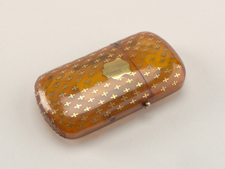 Oblong, with curved lid and rounded corners, semi-transparent, featuring gold piqué work in cross-like pattern all over box body, small gold shield attached to front. Lid hinged on left side. Gold release button on right side. Striker carved into box bottom.
