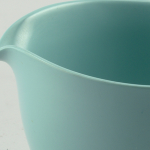 Blue-green creamer with curved spout and outturned handle and rim.