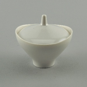 Eggshell-colored (a) softly rounded flaring sugar bowl with edge cut in boat-like shape above inner rim. (b) lid: culminating in plain, truncated knob.
