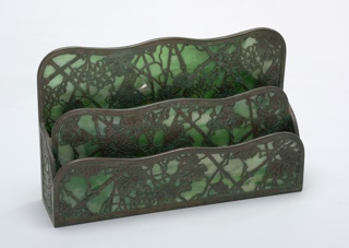 One piece of a six-piece desk set. Letter file of favrille glass and bronze in a grapevine pattern. File has three compartments in a stepped configuration.