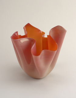 Rose colored vase in the shape of an upside-down rippled handkerchief.