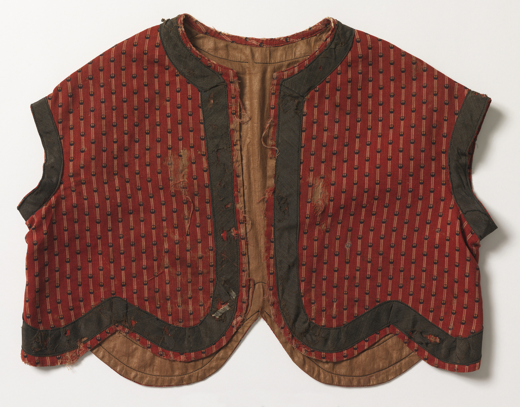 child's short jacket of red wool, striped in white and printed, over-stripe in small black dots. Roud neck, no sleeve, shaped, scalloped bottom. Trimmed with band of black wool around neck, arm hole and bottom, light brown glazed cotton lining. Machine sewn.