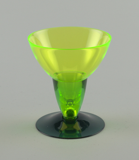 Yellow and green tapered drinking glass with dark green foot and yellow wide mouth.