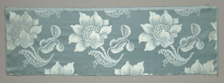 Satin fabric with a staggered horizontal repeat of large-scale blossom, leaf and stem.