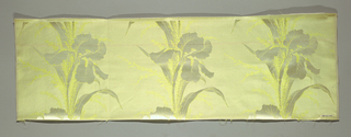 Narrow sample of a horizontally ribbed ground with a single row of three iris flowers and feathery ferns in satin weave. In light gray and yellow.
