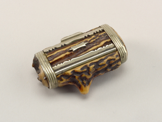 Oblong, snuff box style box, its body comprised of pieces of hollowed out antler, the lid framed in decoratively cut metal with a thumb catch at its front and a small unadorned plaque attached to its top. The sides are attached to the main body with continuous ribbed bands that wrap around the irregular, slightly tubular container. Matches were likely intended to be struck on highly textured box body itself.