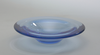 Shallow, thick, circular blue glass bowl with two ridges.