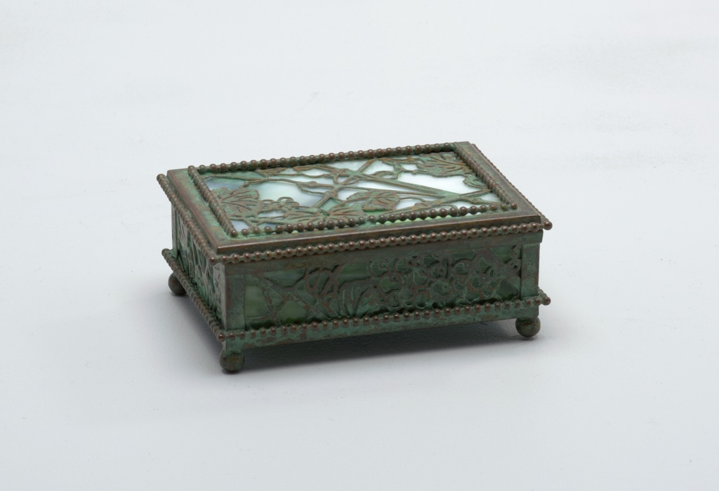 One piece of a six-piece desk set. Box of favrille glass and bronze in a grapevine pattern. Box stands on ball feet and has beaded edges.