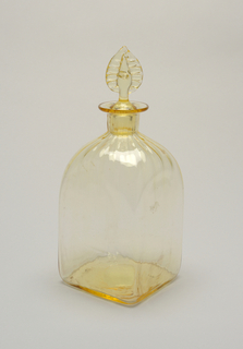 Decanter (a) of rectangular form with slight ridges at shoulder, circular neck and mouth; leaf-shaped stopper (b); all of clear, topaz-colored glass.