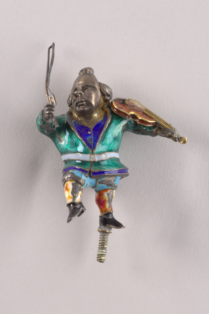 Metal figurine of bald-pated man with top knot holding bow and brown enamel violin with gold strings and edging. Enameled costume: green jacket with gray blet, royal blue waistcoat with gold buttons, light blue breeches, white stockings with red and yellow mottling, black shoes. Threaded pin on base of left foot. Traces of gilding on neck, throat and violin bow.