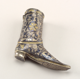 In the shape of a high boot, with stylized floral and vine decoration in niello and gilding.  Lid is on top, hinged on back side.  Striker on sole of toe section.