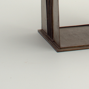 Three-shelf unit with scrolled sides, metal with applied decoration.