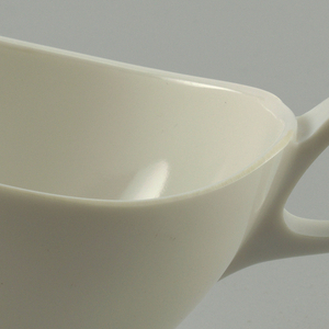 Eggshell-colored boat-shaped, oval creamer with loop handle, all molded in one piece.