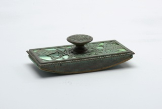 One piece of a six-piece desk set. Rectangular blotter with button handle decorated with green grapeleaf pattern.