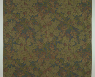Length of upholstery fabric with all-over pattern made up of rows of flowering trees connected in alternate alignment to a row with a second type of flowering tree, in shades of green and red super-imposed on a small scale leaf pattern of blue, green, and violet on black background. Woven imitation of wool needlepoint. Ends finished with machine stitches.