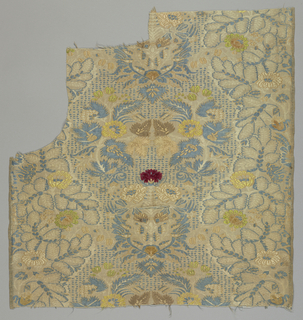 Fragment with large scale symmetrical floral pattern in cream and blue with details brocaded in yellow and brown, on a bone colored ribbed ground. Bright red flower in chenille at center.