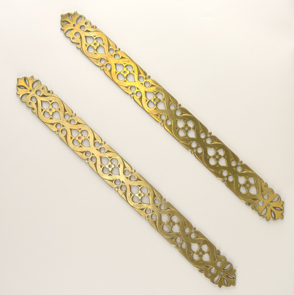 Long, narrow pierced finger plates with stylized Gothic flower and foliage design.