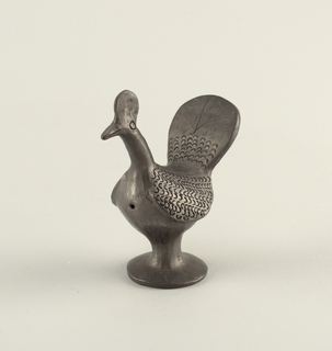 Whistle in the form of a bird with a long neck and upright comb. The feathers are suggest by a series of C-shaped impressions. The tail shows scrolling incised decorations. One hole on the bird's breast, another at back.