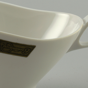 Eggshell-colored boat-shaped, oval body with loop handle, all molded in one piece.