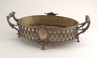 Adam style oval planter with scroll handles; pierced bell flower decoration and center crest. Silver-plated liner.