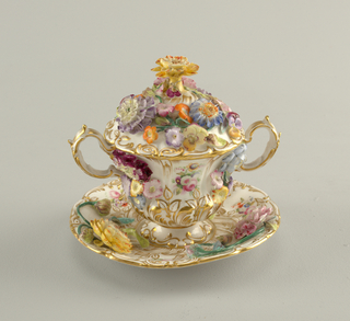 a) Flaring cup with scrolled foot and handles; applied and painted flowers  b) Domed cover with applied flowers, marigold forming knob c) Saucer with applied and painted flowers. Gold scrolls and edges on all three pieces