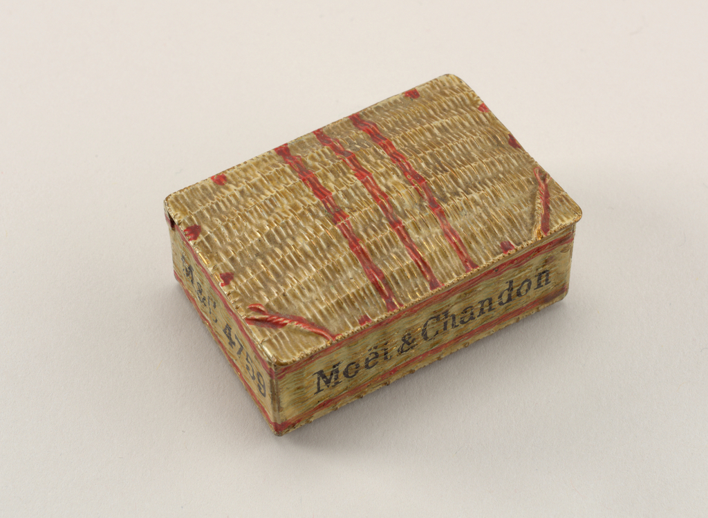 """Rectangular, snuff-box type container, in the form of a champagne hamper, with simulated raised wicker effect, enameled in light brown. """"Moët & Chandon"""" enameled in black on front panel, """"EPERNAY"""" enameled in black on right panel, """"M&C 4759"""" enameled in black on left panel. Double, red enamel  bands, framing inscriptions, extend around perimeter of box. Three red bands painted down center of lid. Additional red marks punctuate four sides of lid. Two simulated, twisted wires at the front corners of lid enameled in red. Lid, attached to spring mechanism, hinged on back. Textured underside likely intended for striker."""
