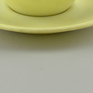 Yellow cup with outturned handle and saucer with impression for cup.