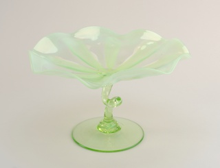 Yellow-green opalescent form of shallow, circular, wavy-edged bowl on green stem with loop in center and circular foot.