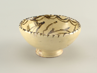 Rounded bowl on foot. Red clay covered with white slip and transparent glaze; three fish and wavy lines painted inside the bowl, with dots and festoons on rim.