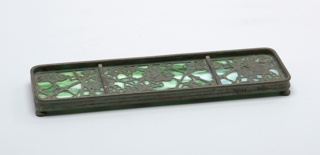 One piece of a six-piece desk set. Pen tray of favrille glass and bronze in a grapevine pattern. Tray is shallow and rectangular and divided into three sections, the middle being the largest.
