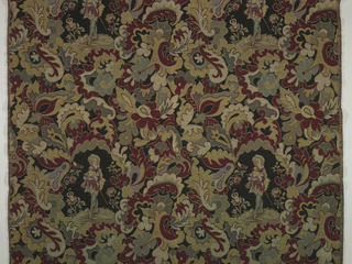 Length of upholstery fabric with elaborate, stylized leaf forms of red, gold, green and grey framing a standing cavalier surrounded by smaller, more naturalistic flowers, in rows, one above the other. Woven in imitation of wool needlepoint. Black background. Square repeat of a more or less square pattern unit.