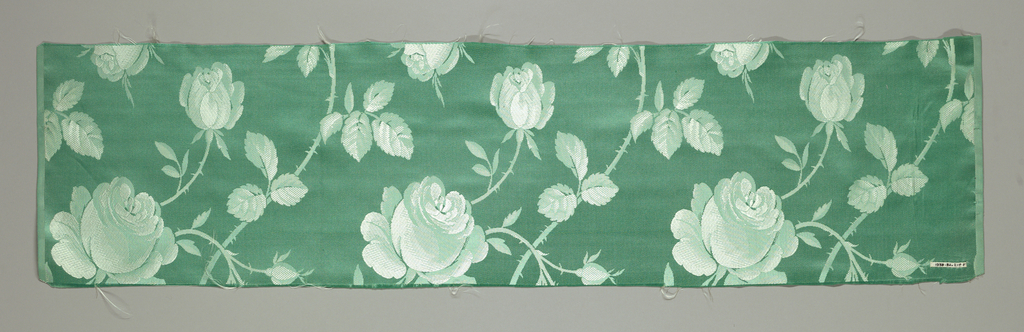 Textile has a satin foundation and an allover large-scale repeat of realistically rendered roses and buds woven in plain weave with short weft floats.
