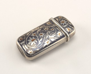 Oblong, with rounded sides and corners, featuring silver, winding, flowered tendrils attached to larger, central, paisley motif, center of flower forms punctuated with copper, all on darker steely-gray ground; reverse features same decoration. Lid, hinged on side, has protruding, rounded lip running along its lower edge; initials, possibly YM, engraved on lid top. Small, oval shaped striker on bottom.