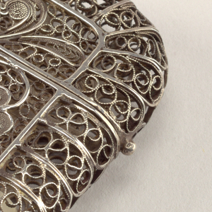 Oblong, curved sides and lid, structure of lacy, silver filigree work, featuring a central, vertical, rectangular area with a single, long-stemmed flower and leaves, identical on front and reverse. Lid, upper third of box, hinged on side, small knob-like thumb catch opposite. Small oval striker on bottom.
