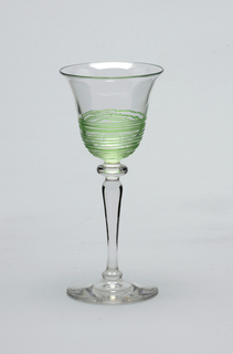 Clear glass, circular base, tall baluster-shaped stem, bowl with sides flaring out towards rim. Light green threading applied to outside of lower section of bowl.