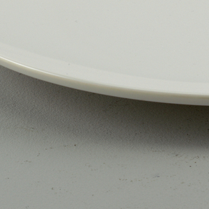 Eggshell-colored plain dinner plate, so called coupe shape, without distinction between center and marli. Edge reinforced.