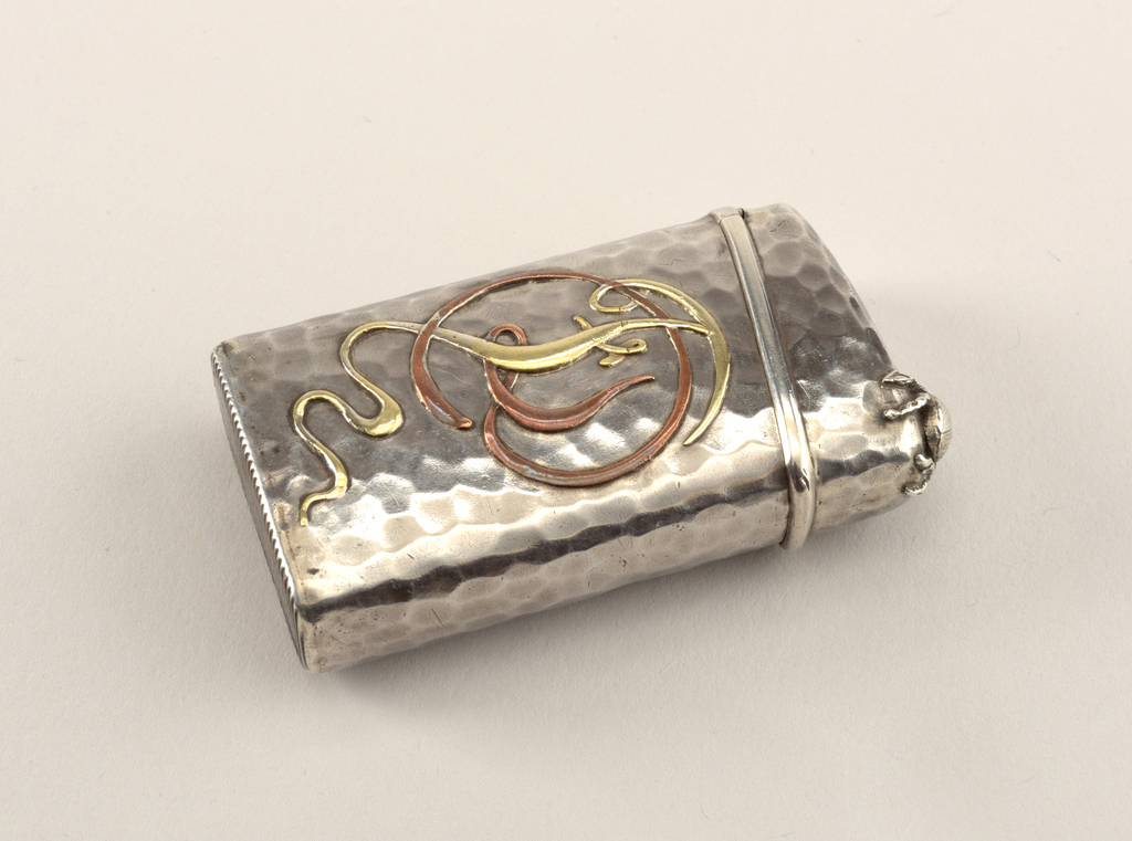 Matchsafe in Japanese style. Oblong, rounded corners, with overall hand hammered surface, featuring applied decoration of a copper maple leaf and brass maple seed on front side, small applied beetle on top corner of lid, stylized monogram (FD) in brass and copper on reverse. Lid, hinged on side, opens on the diagonal. Striker on bottom.