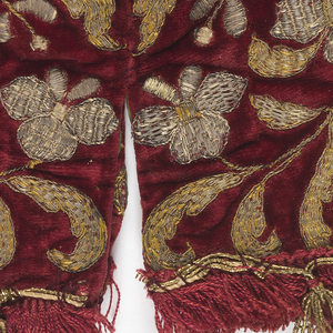 Conical-shaped cover for a chalice made in four sections. Red velvet, embroidered in gold in a stylized plant design. Fringe and tassels of silk and gold. Lined with green silk.