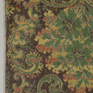 Scrolls form a large-scale loose ogee lattice which frame palmettes. Colors are green, dark brown, yellow, and red.