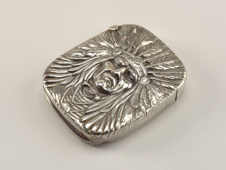 Oblong, with rounded corners, featuring depiction of Native American man in feathered head dress. Reverse features no decoration except for an elaborate incised monogram (RR ?). Lid (upper section of box) hinged on side. Striker recessed into bottom.