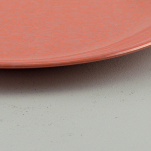 Reddish-orange plastic plate with extended sides to serve as handles.