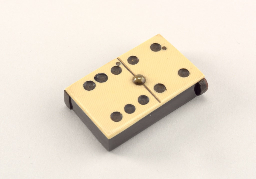 "Rectangular, in the form of a beige domino game piece with ten black dots, four above black, incised, horizontal line in center, six below, with brass bolt situated at center of incised line. Sides and reverse are black, reverse inscribed ""Bull & Bell Ropemaker, With E. Cuthbert's Compts."" Lid hinged on left side, end protrudes slightly on right for thumb catch. Striker on left vertical side."