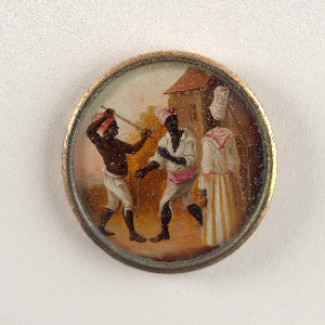 Button depicting scene of figures in a landscape with a building. A shirtless man wearing a red turban and white pants fighting with a wooden stick with another man wearing white pants and striped turban as he looks to a woman who is facing both men. She wears a striped red and white scarf around her neck, orange and white skirt.