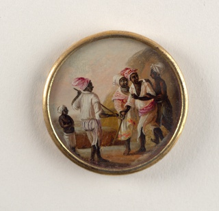Button depicting scene with five figures. Two men wear white clothing and pink turbans and are training with wooden sticks, looking at their left [proper]. Behind them, a woman in a skirt, shirt and white turban also faces the same direction. On each side, two shirtless men stand wearing pants and turbans.