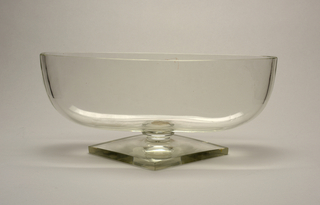 Oval bowl on lozenge-shaped foot, all of thick clear glass.