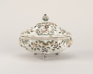Shaped ovoid tureen on three feet; stepped, domed cover with central knop; green and ochre decoration of birds, flowers and foliage.