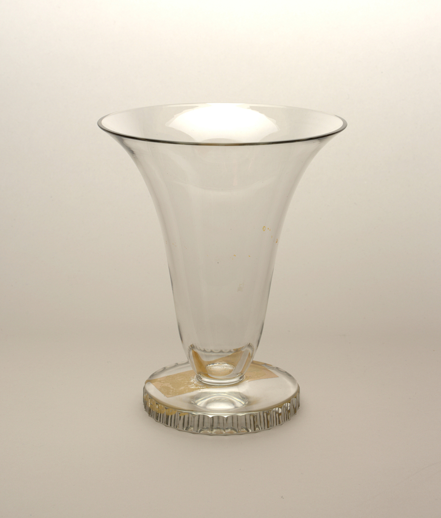 Blown glass footed vase with cut glass detail along rim of base.